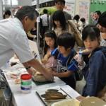 日本の伝統食材であるかつお節削りを体験。かつお節削りは初体験という子どもも多い