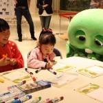 ワークショップでガチャピンに見守られながら絵を描く子どもたち