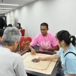 ピンク色のTシャツの男性はスリランカ出身。子ども時代から親しんできたキャロムを伝授